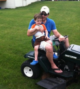 dad-with-son-on-lap-on-riding-mower